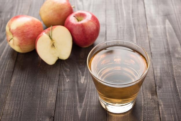 Bebida de suco de maçã saudável e frutas maçãs vermelhas na mesa de madeira Foto Premium