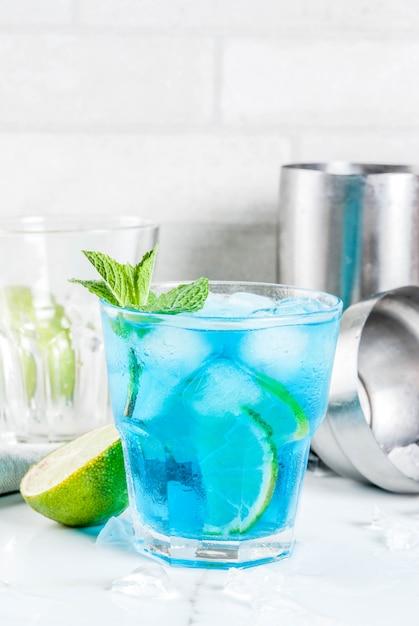Bebida de verão colorido, gelado azul lagoa álcool cocktail bebida com limão e hortelã Foto Premium