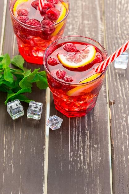 Bebida de verão com framboesas, limão e gelo em uma velha mesa de madeira Foto Premium
