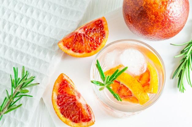 Bebida de verão com laranja de sangue e alecrim no fundo branco de madeira Foto Premium