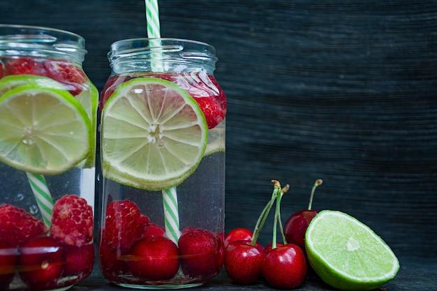 Bebida de verão refrescante com frutas. bebida feita de cereja, framboesa, limão. fundo de madeira escuro. Foto Premium