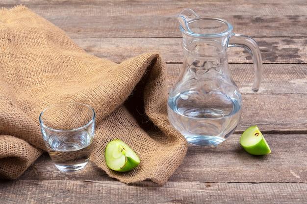 Bebida dietética de desintoxicação com fatias de maçã em água limpa e uma maçã fresca em uma mesa de madeira, close-up Foto Premium