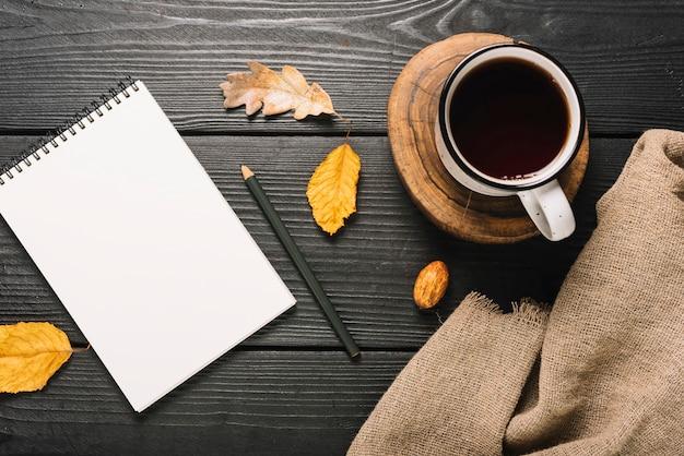 Bebida e pano perto de folhas e artigos de papelaria Foto gratuita