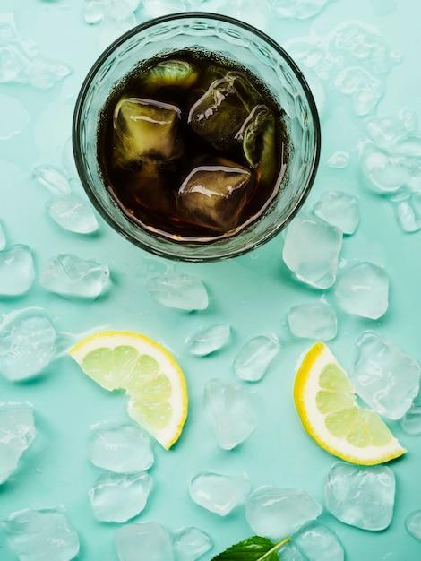Bebida em vidro perto de limões e blocos de gelo Foto gratuita