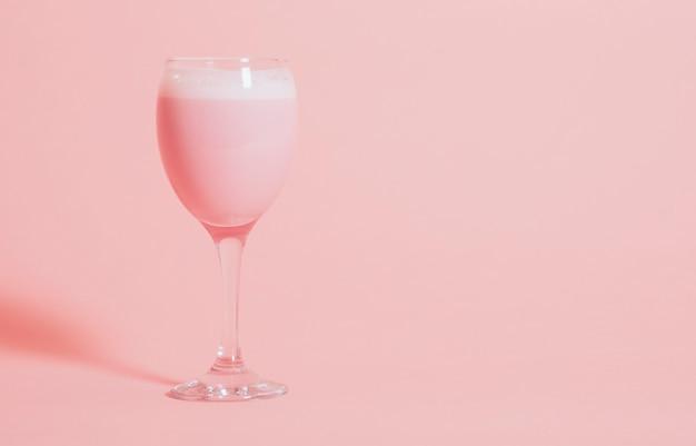 Bebida extravagante rosa fofo em um copo de vinho Foto gratuita