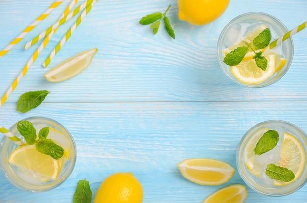 Bebida fria de verão refrescante com limão e hortelã na luz azul de fundo de madeira Foto Premium