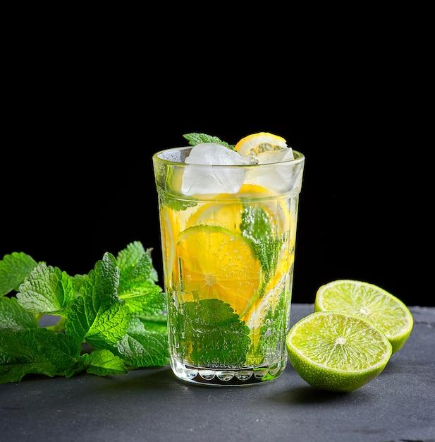 Bebida gelada feita a partir de pedaços de limão, limão e folhas de hortelã verde em um copo com gotas de água Foto Premium