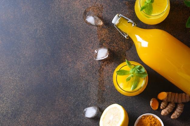 Bebida herbal indonésia de jamu com ingredientes naturais açafrão, gengibre no fundo marrom. espaço para texto. Foto Premium