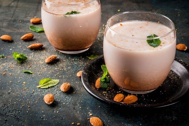 Bebida indiana tradicional, comida de festival de holi, thandai sardai bebida de leite com nozes, especiarias, hortelã. fundo azul escuro, cópia espaço Foto Premium