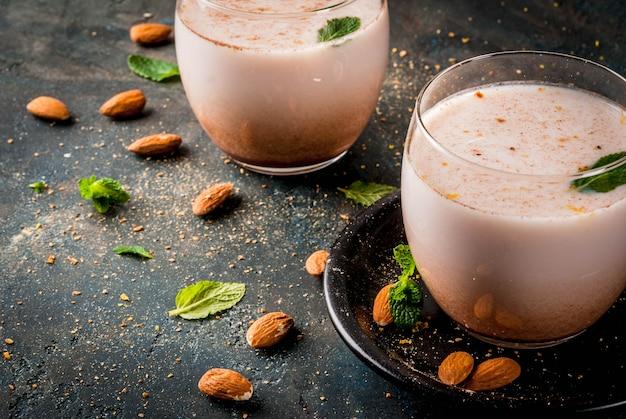 Bebida indiana tradicional, comida de festival de holi, thandai sardai leite bebida com nozes, especiarias, hortelã. superfície azul escura, cópia espaço Foto Premium