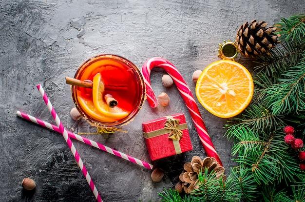 Bebida quente com vinho quente com laranja e decorações de natal Foto Premium
