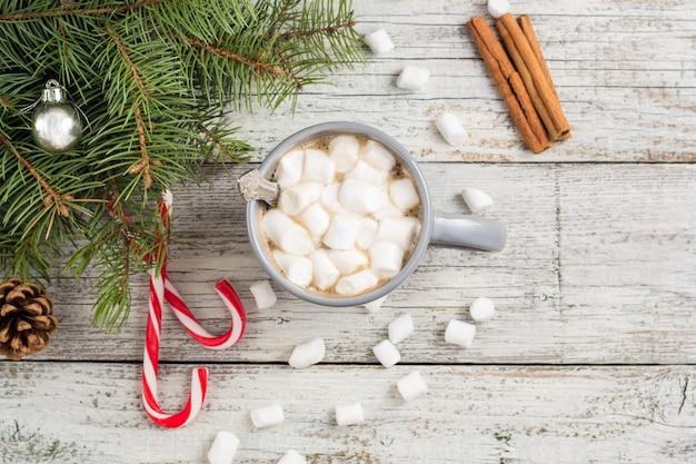 Bebida quente de inverno. chocolate quente de natal ou cacau com marshmallow em branco com decorações de natal Foto Premium