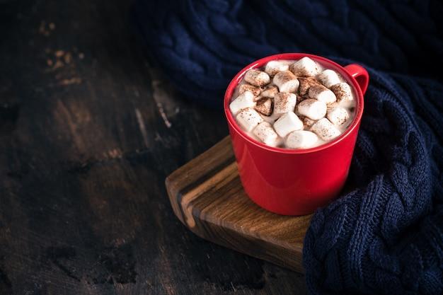 Bebida quente de inverno ou outono, chocolate quente ou cacau, marshmallow e blusa de malha Foto Premium