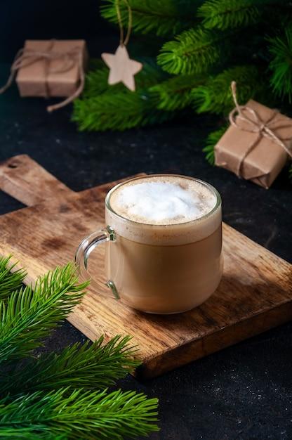 Bebida quente de natal. cacau, café ou chocolate em copos na mesa escura com caixa de presente e ramos de abeto. Foto Premium