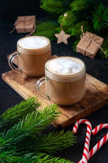 Bebida quente de natal. cacau, café ou chocolate em copos na mesa escura com doces, caixa de presente e ramos de abeto. Foto Premium