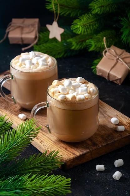 Bebida quente de natal. cacau, café ou chocolate em copos na mesa escura com marshmallows, caixa de presente e ramos de pinheiro. Foto Premium