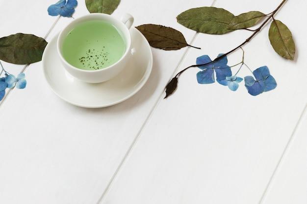 Bebida quente verde natural com rosas e plantas na mesa Foto gratuita