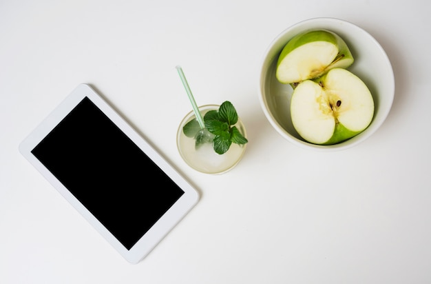 Bebida refrescante com maçãs e tablet Foto gratuita