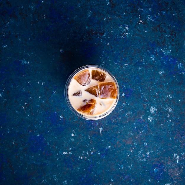 Bebida refrescante de verão frio com gelo e leite de café sobre uma mesa azul Foto Premium