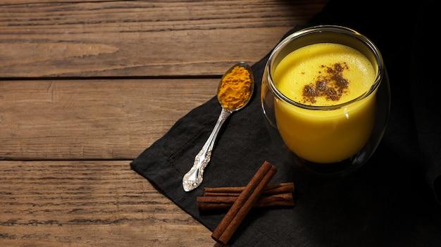 Bebida saudável com leite, açafrão, canela, pimenta, cravo. bebida tradicional indiana Foto Premium