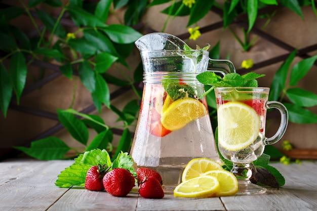 Bebida saudável do verão fresco com limão e morangos com gelo. Foto Premium