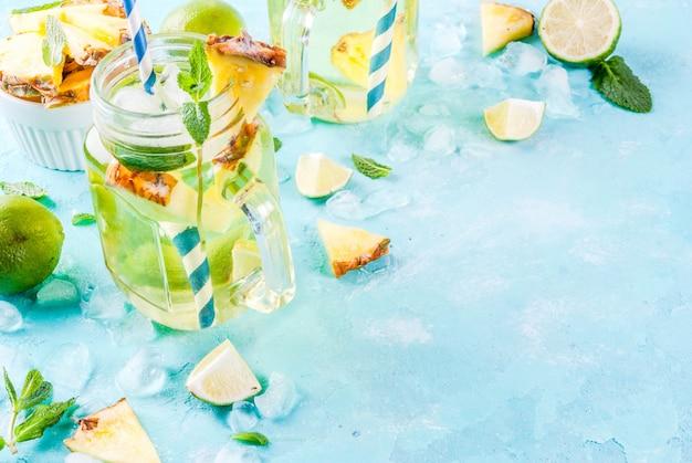 Bebida tropical mojito de abacaxi ou limonada com limão fresco e hortelã fundo azul claro Foto Premium