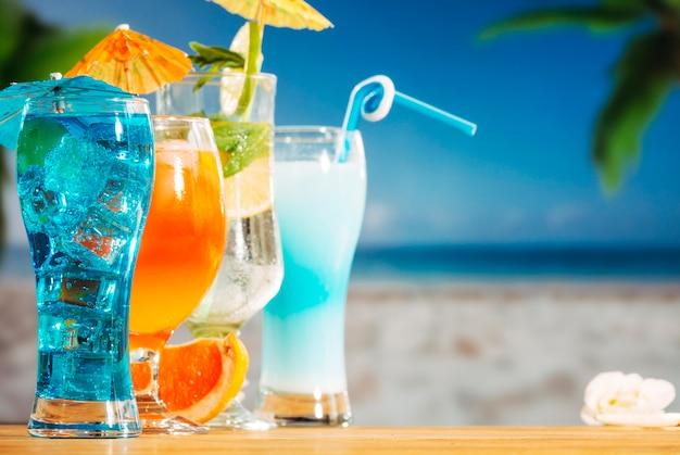 Bebidas de laranja azul com cubos de gelo de hortelã limão cortados em guarda-chuva brilhante decorado óculos Foto gratuita