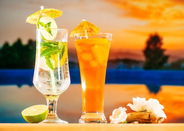 Bebidas de laranja frescas com cubos de gelo de hortelã de limão fatiado e flores brancas Foto gratuita