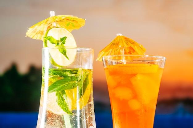 Bebidas de laranja frescas com cubos de gelo de hortelã de limão fatiado Foto gratuita