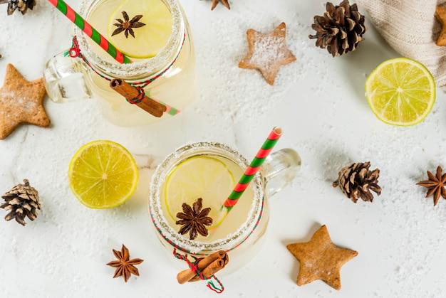 Bebidas de outono e inverno. bebida de férias de natal. cocktail festivo de bolas de neve com estrelas de suco de limão, canela, licor, açúcar e anis. na mesa branca com decoração de natal, copyspace vista superior Foto Premium