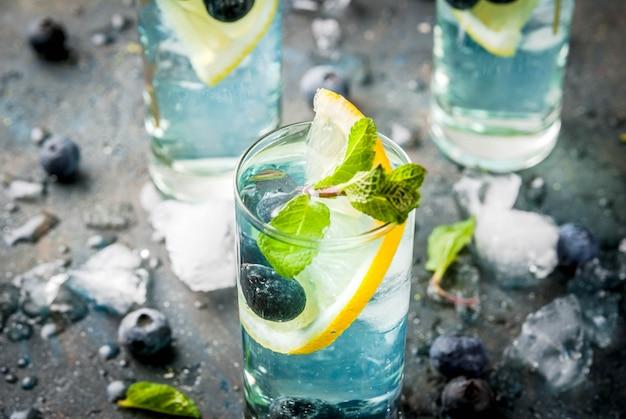 Bebidas de refresco de verão, limonada de mirtilo ou mojito cocktail com limão, mirtilos frescos e hortelã, copyspace de pedra azul sdark Foto Premium