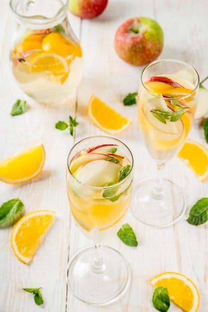 Bebidas e coquetéis. sangria de outono branca com maçãs, laranja, hortelã e vinho branco. em copos de champanhe, em uma jarra, em uma mesa de madeira branca. Foto Premium