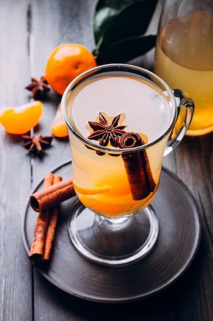 Bebidas frescas com especiarias, frutas cítricas e canela em vidro na madeira Foto Premium