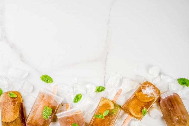 Bebidas refrescantes congeladas receita de picolés de coquetel de verão cuba libre chá doce frio ou café com folhas de hortelã e limão Foto Premium