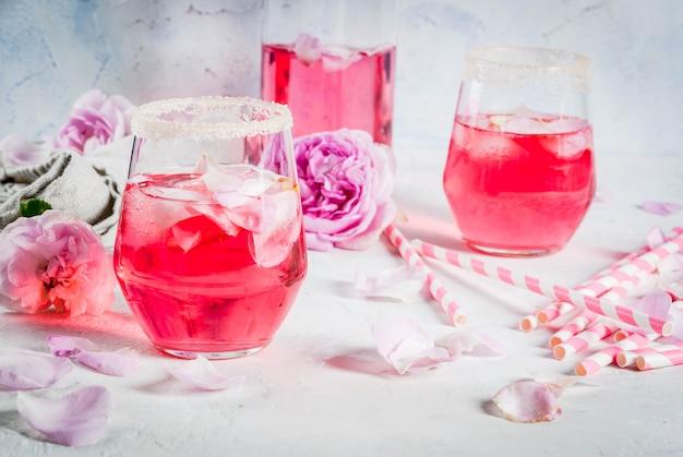 Bebidas refrescantes de verão coquetel rosa claro com vinho rosé chá pétalas de limão em uma mesa de concreto de pedra branca com túbulos listrados rosa pétalas e flores rosas Foto Premium