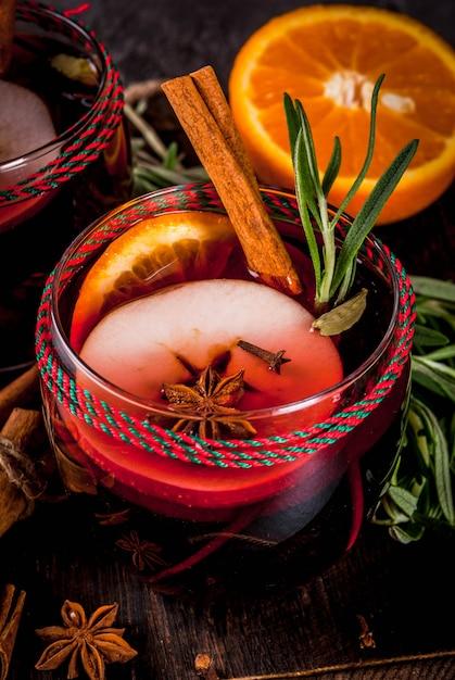 Bebidas tradicionais de inverno e outono. cocktails de natal e ação de graças. vinho quente com laranja, maçã, alecrim, canela e especiarias sobre um fundo escuro de pedra, copie a vista superior do espaço Foto Premium