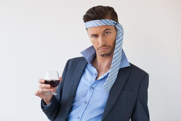 Bebido homem de negócio com laço na cabeça e vidro Foto gratuita
