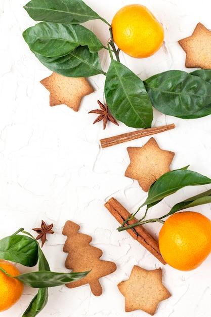 Beira de biscoitos da estrela do natal com especiarias e mandarino na superfície branca com copyspace. Foto Premium