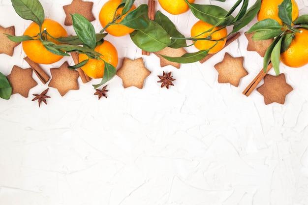 Beira de biscoitos da estrela do natal com especiarias e mandarino no fundo branco com copyspace. Foto Premium