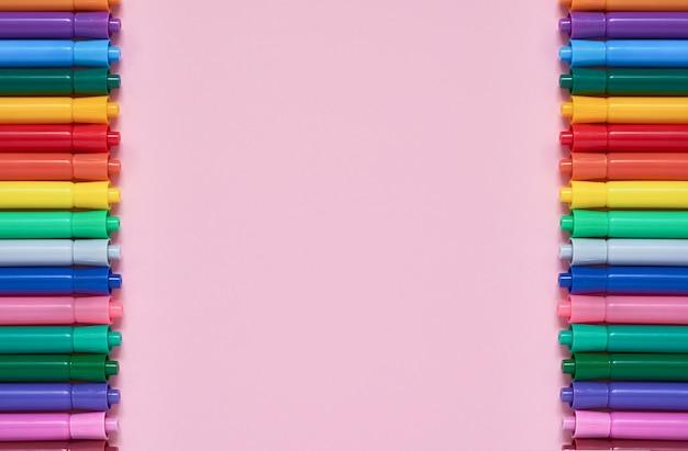 Beira de penas de ponta de feltro coloridas no fundo cor-de-rosa com copyspace. vista do topo Foto Premium