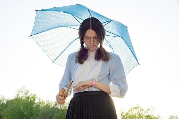 Bela adolescente com um guarda-chuva olha para o relógio de pulso Foto Premium