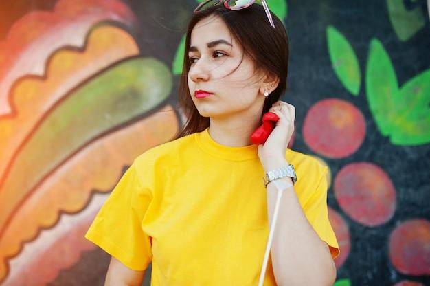 Bela adolescente em t-shirt amarela perto da parede do graffiti. Foto Premium