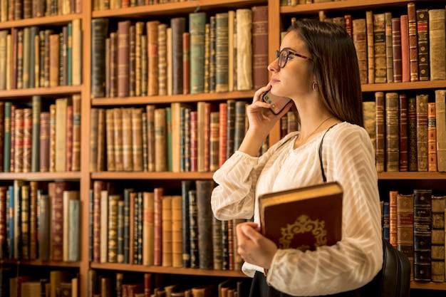 Bela aluna com livros falando no telefone na biblioteca Foto gratuita