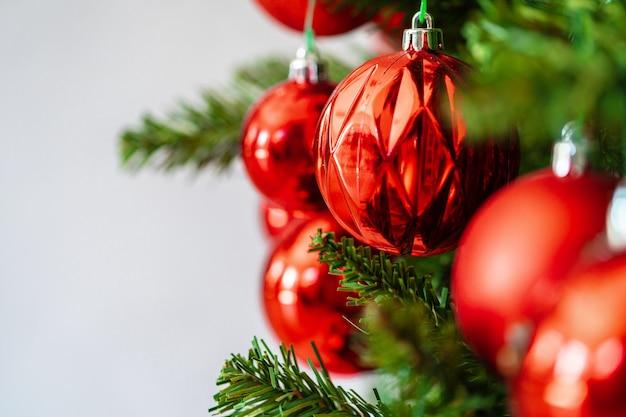 Bela árvore de natal com enfeites vermelhos close-up Foto Premium
