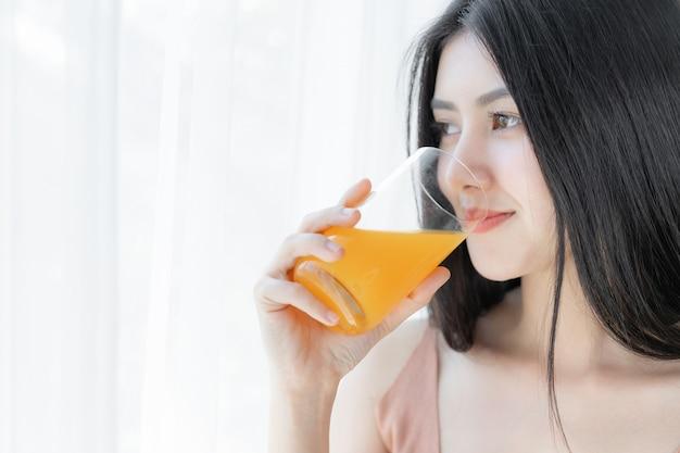 Bela beleza mulher asiática linda garota se sentir feliz bebendo suco de laranja para uma boa saúde de manhã Foto gratuita