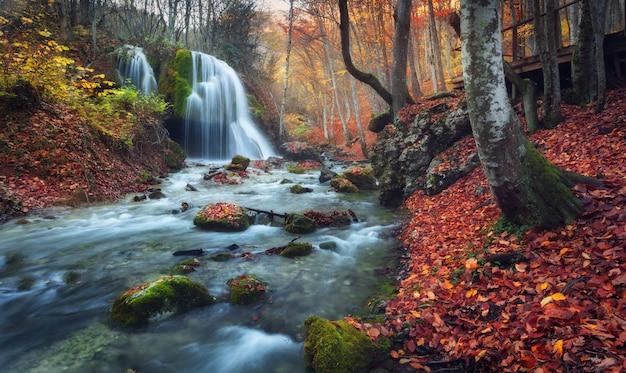 Bela cachoeira na floresta de outono nas montanhas da crimeia ao pôr do sol Foto Premium