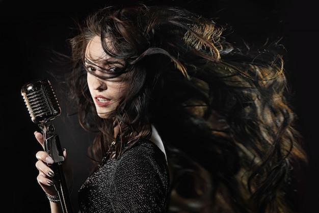 Bela cantora com um microfone e cabelos esvoaçantes Foto Premium