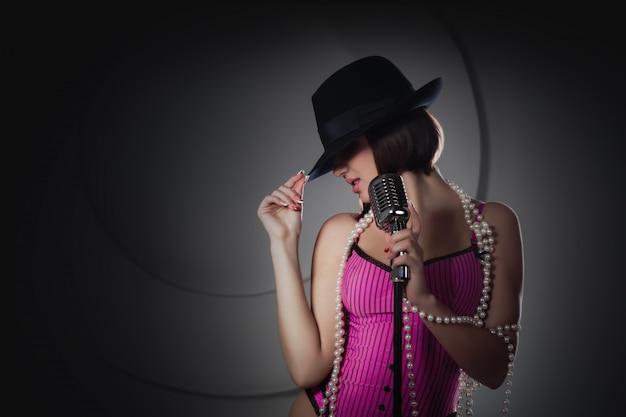 Bela cantora de chapéu preto, cantando com um microfone retrô Foto Premium