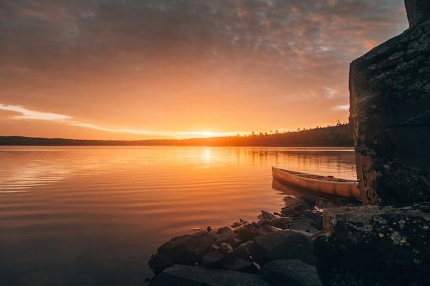 Bela chance de uma canoa em um lago perto de colinas de pedra durante o pôr do sol Foto gratuita