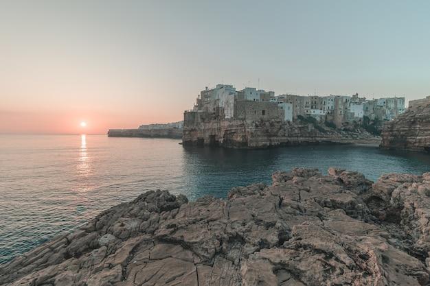 Bela cidade em um penhasco à beira-mar com o pôr do sol no fundo Foto gratuita